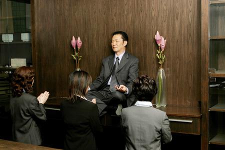 Women worshipping a businessman who is sitting on the shelf meditating  Reklamní fotografie