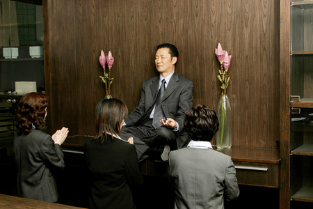 Women worshipping a businessman who is sitting on the shelf meditating  photo