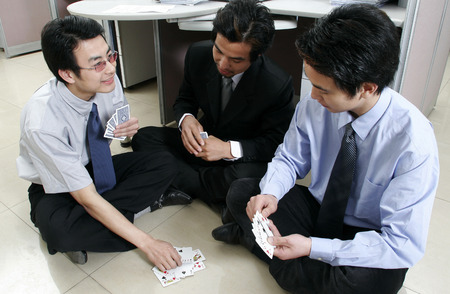 Three men playing cards in the office  photo