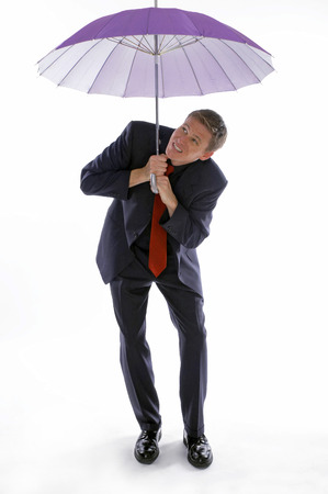 Man in business suit holding an umbrella while checking the weather