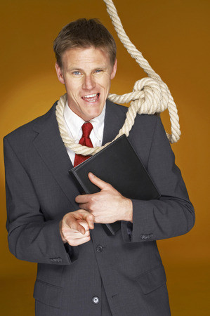 Businessman pointing at the camera while a rope hanging around his neck  photo