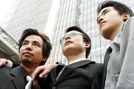 desirous: Low angle view of three businessmen standing in front of the building  Stock Photo