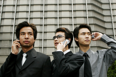 Three businessmen talking on the hand phones  photo