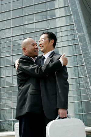 Two businessmen hugging each other
