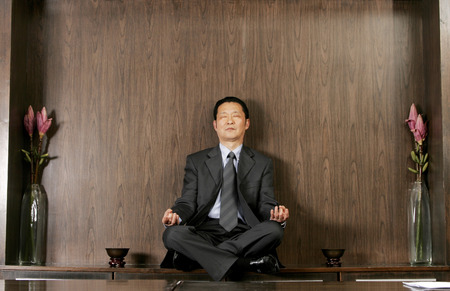 Man in business suit sitting on the shelf meditating  photo