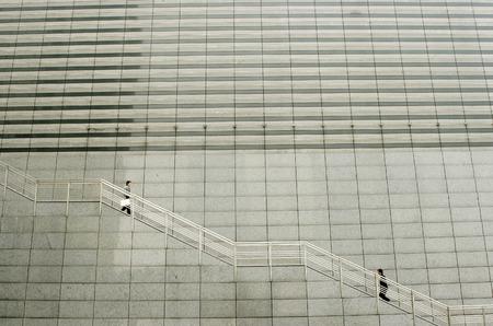 going down: Un hombre que va para arriba mientras que la otra va por las escaleras