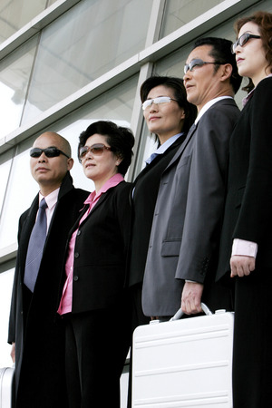 Business men and women in sunglasses standing in a row  Stock Photo