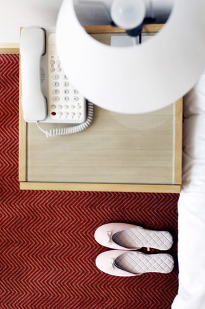 Top view of a pair of pink shoes beside the bed  photo