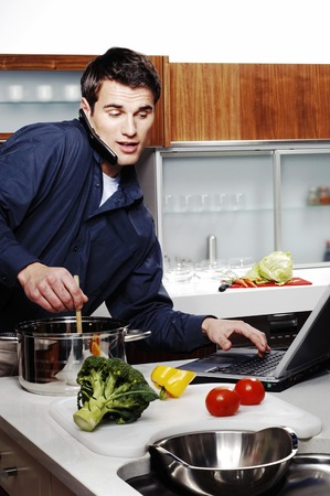 Man cooking, using laptop and talking on the hand phone at the same time photo
