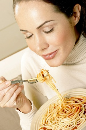 Woman enjoying a bowl of spaghetti photo