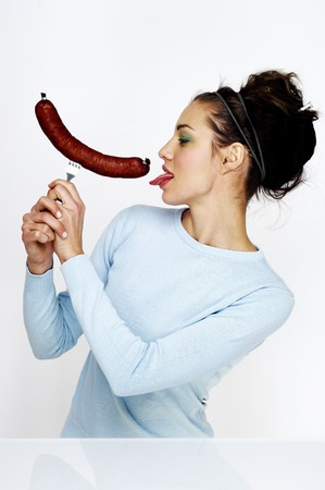 Woman licking a long sausage