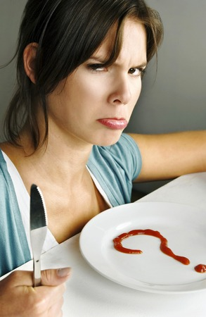 Woman with angry face sitting in front of a question marked plate