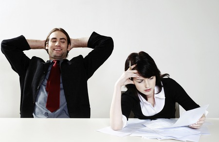 workmate: Businessman relaxing while his colleague is busy with her work