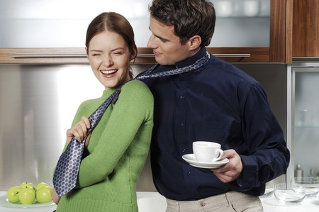 Woman pulling her boyfriends tie photo