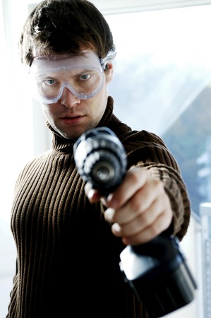 Man with goggles pointing a drill at the camera photo