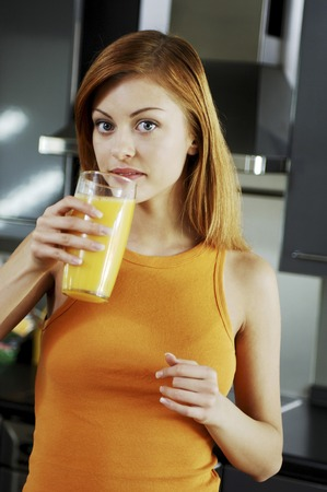 replenish: Woman about to drink a glass of orange juice Stock Photo