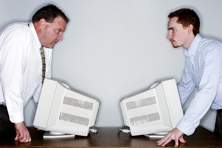 Two businessmen looking at each other angrily photo