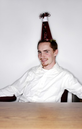 Businessman with party hat smiling at the camera photo