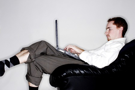 Businessman sitting on the couch using laptop photo