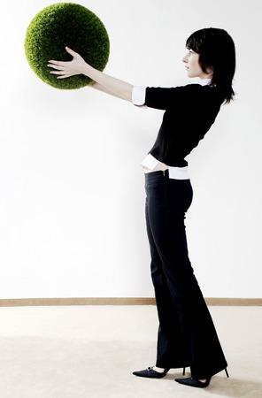 Businesswoman holding a grass ball