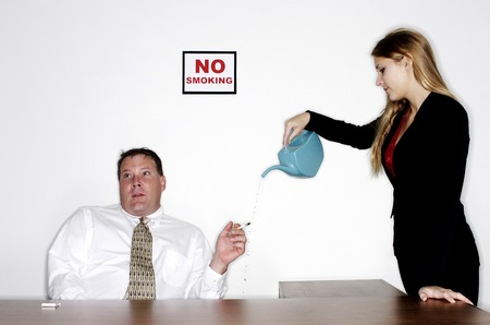 ignorant: Businesswoman watering the cigarette from an ignorant businessman