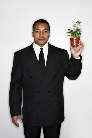 Businessman holding a pot of plants