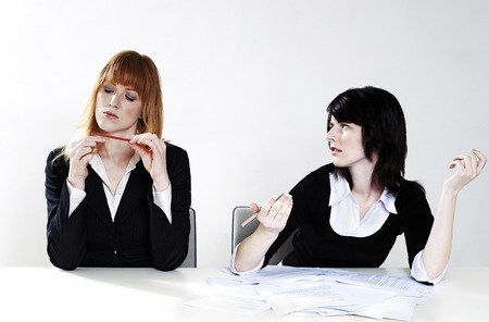 Businesswoman getting frustrated with her colleague for not doing her work photo