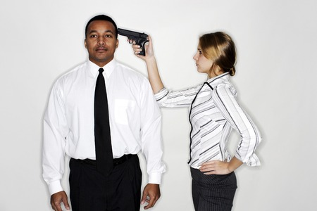 Businesswoman pointing a gun at her subordinates head photo