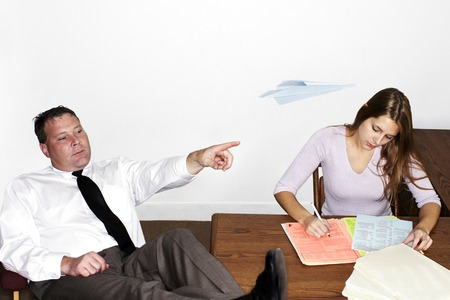 Businessman playing with paper plane while his colleague is busy working