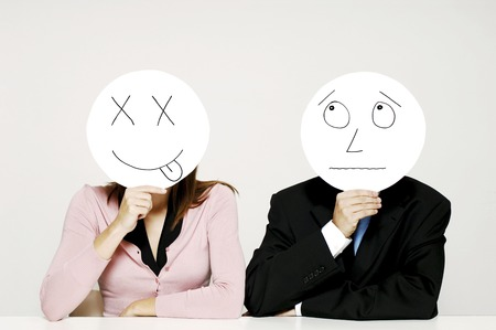 teasing: Business people holding cardboard cutout with facial expression Stock Photo