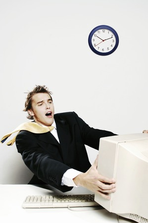blown away: Businessman being blown away by the desktop computer Stock Photo