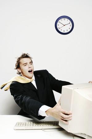 blown away: Businessman being blown away by the desktop computer Stock Photo