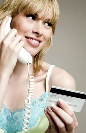 Woman using credit card over the telephone Stock Photo - 26144172