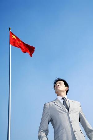 Businessman standing under a flag
