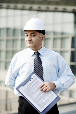 safety helmet: Hombre de negocios mayor que llevaba un casco de seguridad