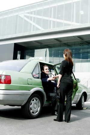 desirous: Businesswoman greeting her client from the taxi Stock Photo