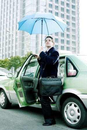 desirous: Businessman holding an umbrella while getting out from taxi
