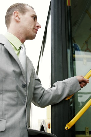 Businessman getting on bus photo