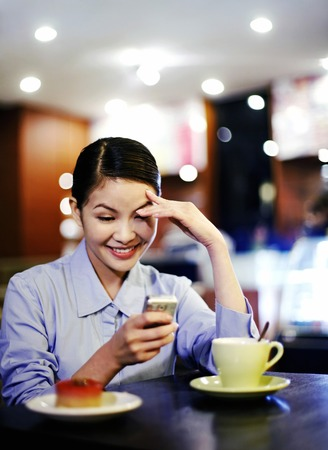 Woman laughing while reading phone messages photo