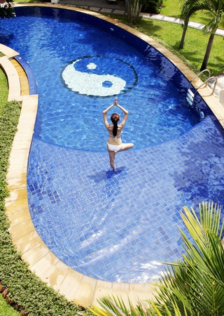 holistic view: Woman practising yoga in the swimming pool