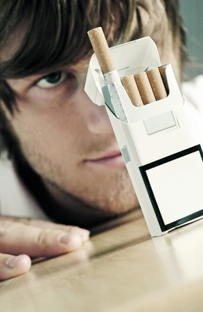 showmanship: Man staring at a box of cigarette Stock Photo