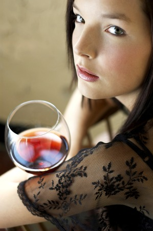 Woman holding a glass of red wine photo