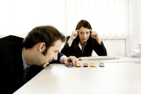 irritating: Businesswoman watching her male colleague playing with his toy cars