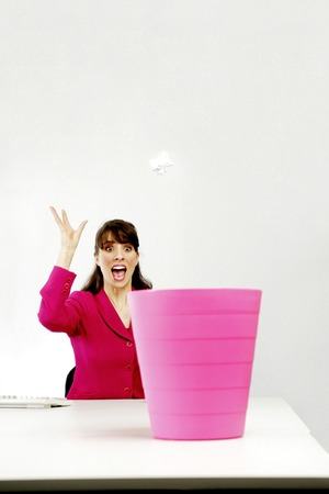 Businesswoman throwing a crumpled paper into a dustbin photo