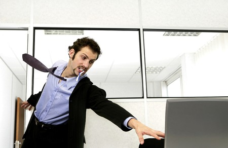 Businessman running in to save his computer photo