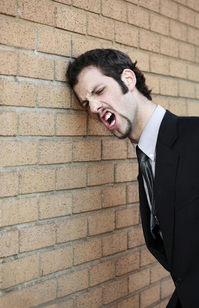 anguished: Businessman banging his head against the wall Stock Photo