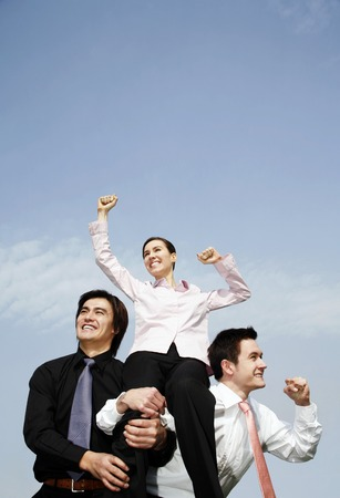 workmate: Businessmen lifting up the female winner