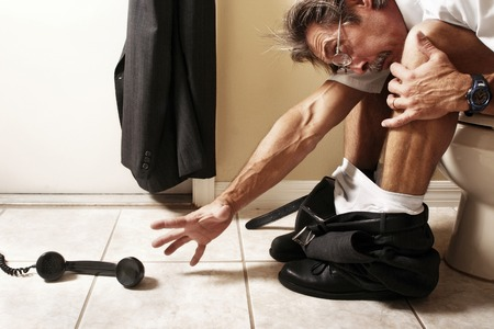 inconvenient: Businessman sitting on the toilet bowl trying to reach for the telephone