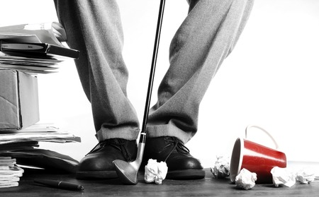 Businessman hitting crumpled papers with golf club