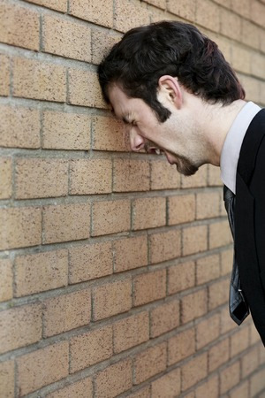 Businessman banging his head against the wall Stock Photo